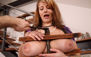 Jane Black shows her tits then gets crushed in a wooden vice